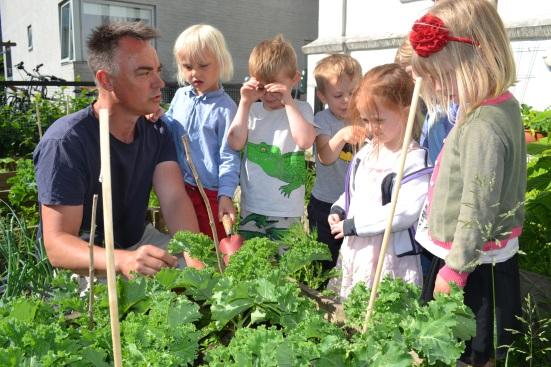 Ole Kassow viser haven frem til børn fra børnehaven Villa Villa i Randersgade.